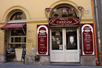 the yellow facade and the white, dark red entrance of the cake shop