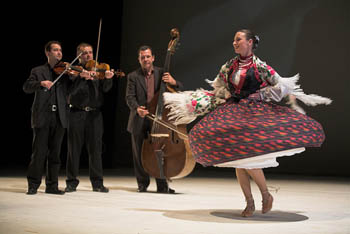 a woman in folk costume dancing on stage, a small orchestra playing in the background