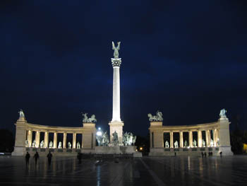 the Millennium monument with the tall column in the middle illuminated at night