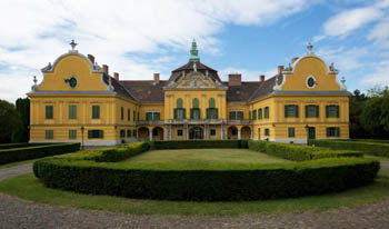 the yellow building of the castle museum and its garden on a clear day