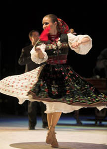 a woman in colorful folk costume performing a folk dance
