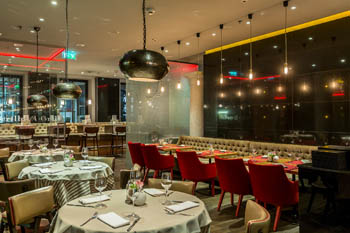 the bar and some set tables inside La Parrilla Restaurant