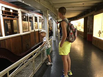 our two boys 8aged 5 and 12) next to a vintage carriage in the museum