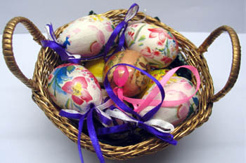 6 painted easter eggs with flower motifs on them placed in a small wicker basket