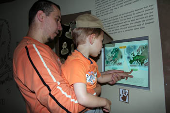 my husband holding our 4 yr boy up to the touch screen on the Ice Age exhibit