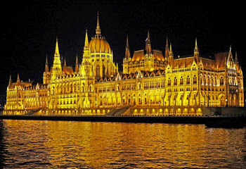 the parliament lighted up at night photographed from the Danube