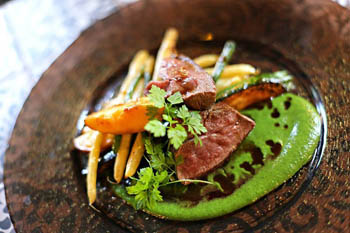 steak slices with asparagus and green pea sauce on a round copper plate
