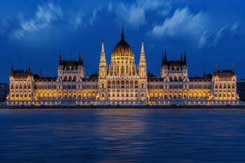 the illuminated front of the Parliament at the blue hour, from the Buda side