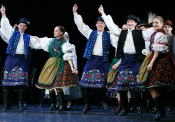 4 folk dance couples on stage dressed in blue/black/white/green costume