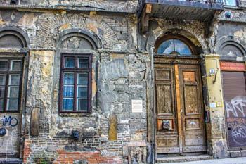 a sahbby vaulted wooden door in a rundown building