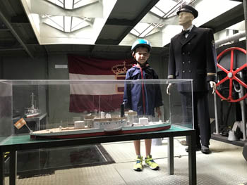 My 7 yr old boy standing beside a mock-up war ship inside a glass cabinet