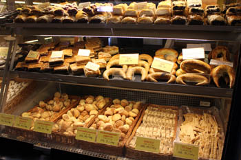 assorted bakery goods (scones, bun, bread roll, strudels) in a glass counter