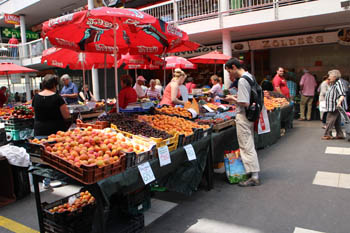vendors selling fresh fruits and vegetables under red umbrellas on a summer day