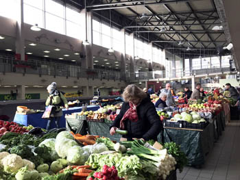 an elderly lady buying veggies in the covered market hall at fehervari ut