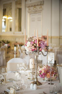 stylishly set white tables with pink flower arrangements and candles in the middle, white clothed chairs around the tables