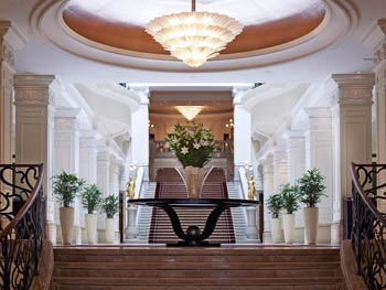 the main lobby with a grand staircase and a huge inverted pyramid shape chandelier hanging form the ceiling, white stuccoed columns along the two sides