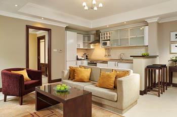 beige sofa, a dark brown coffee table and a dark brwon plush armchair, beige floor