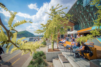 people sitting on the terrace of Bálna in Pest, overlooking the Danube on a sunny summer day