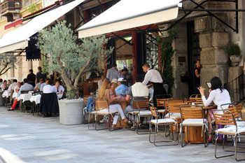 Waiter serving atable on a busy street terrace under beige parasols