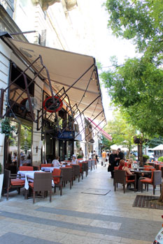 tables and rattan chairs on the street lined with trees