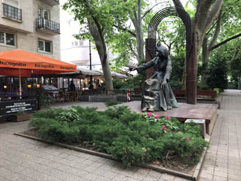 the bronze statue of Franz Liszt sitting, on the square named after him, terraced cafes in the background